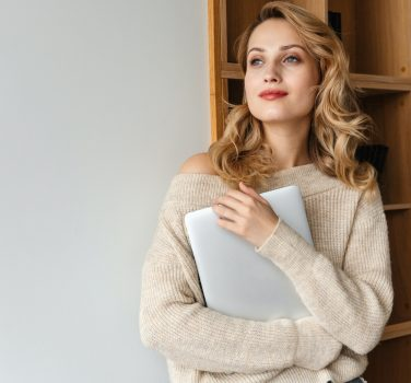 Beautiful young woman indoors at home holding laptop