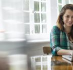 Smiling woman with laptop in home office.
