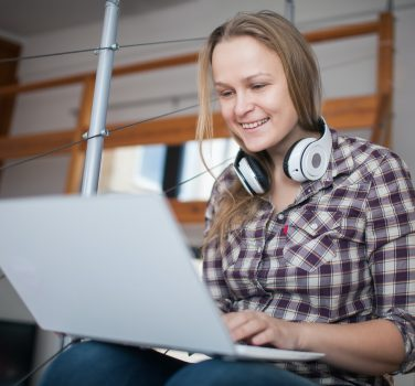 Woman spending leisure time with laptop at home