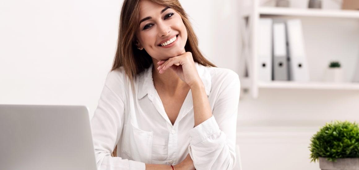 smiling-businesswoman-sitting-at-laptop-posing-at.jpg